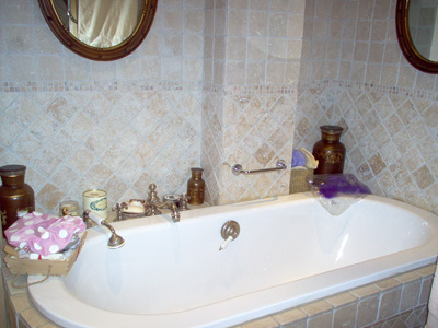 The master bathroom has a bathtub, a built in shower, an old fashioned sink, a WC and beautiful tile work