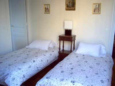 The second bedroom is bright and sunny with large windows. It has two firm twin beds.
